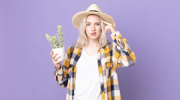 Młoda piękna kobieta albinos czuje się zdezorientowana i zakłopotana, pokazując, że jesteś szalony i trzymasz kaktusa z rośliny doniczkowej