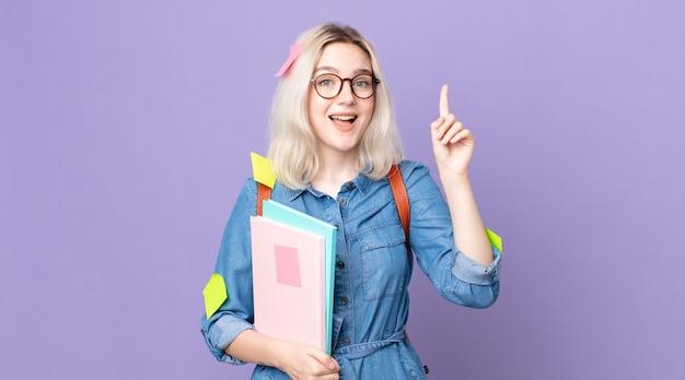 Młoda piękna kobieta albinos, która po zrealizowaniu swojego pomysłu czuje się jak szczęśliwy i podekscytowany geniusz. koncepcja studenta