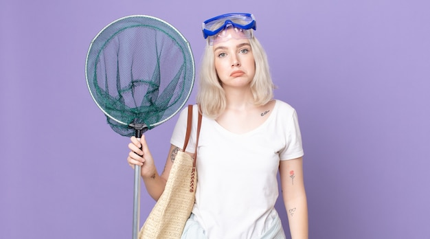 Młoda piękna kobieta albinos smutna i jęcząca z nieszczęśliwym spojrzeniem i płacząca z goglami i siecią rybacką