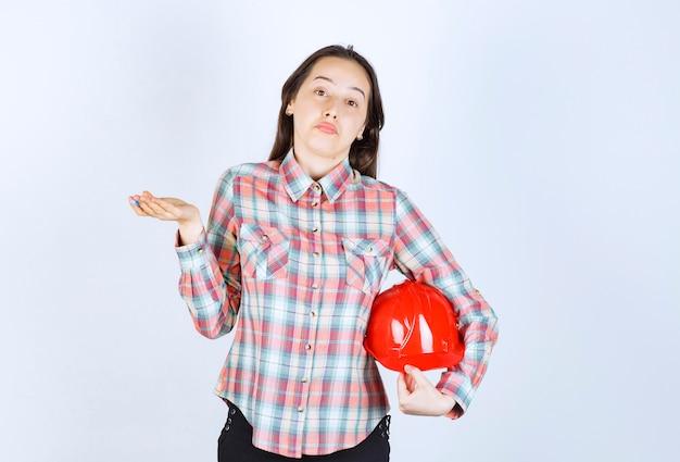 Młoda piękna kobieta architekt trzymając kask i wzruszając ramionami.