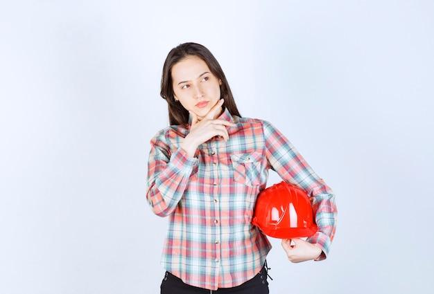 Młoda piękna kobieta architekt trzymając kask na białej ścianie.