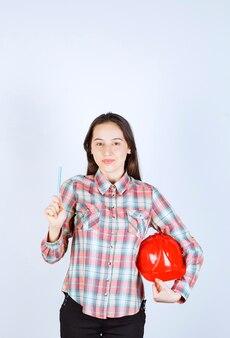 Młoda piękna kobieta architekt trzymając kask z piórem.
