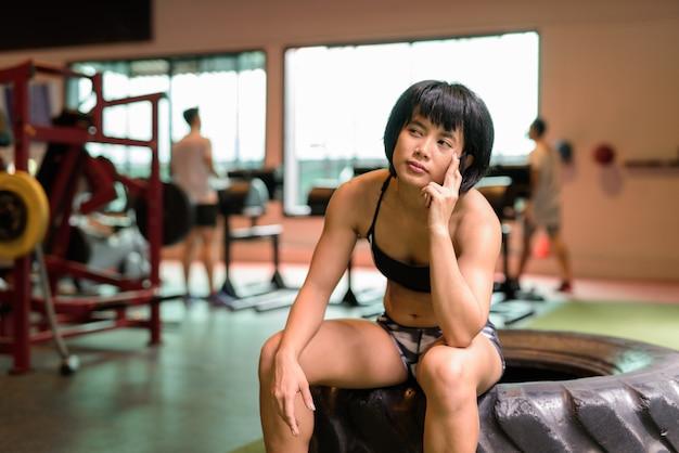 Młoda piękna kobieta azjatyckich fitness siedzi na siłowni