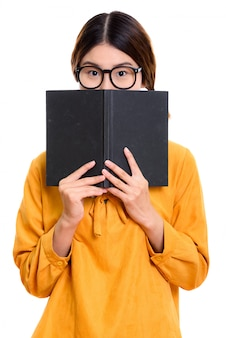 Młoda piękna kobieta azji, chowając się za książką