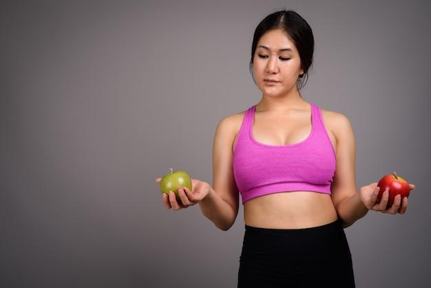 Młoda piękna kobieta azji gotowe do siłowni przed szarej ścianie