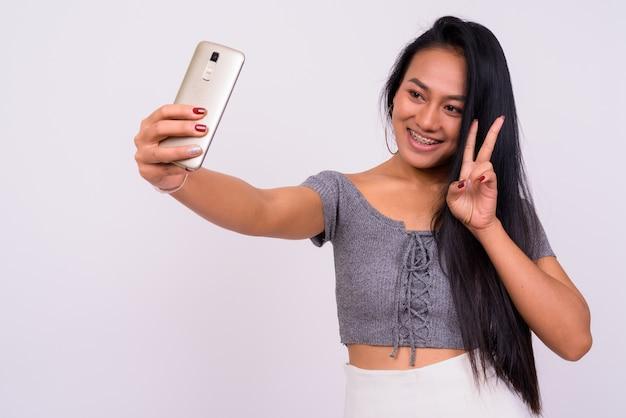 Młoda piękna kobieta azji na białej ścianie