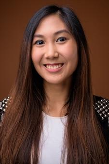 Młoda piękna kobieta azji na brązowym tle