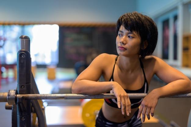Młoda piękna kobieta azji, poćwiczyć na siłowni i myślenia