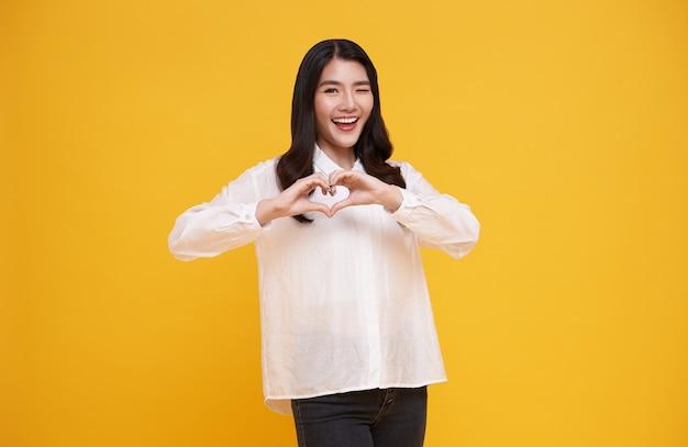 Młoda piękna kobieta azji pokazano znak serca na żółto. koncepcja miłości i szczęśliwych walentynek.