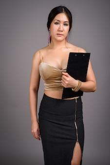 Młoda piękna kobieta azji przeciw szarej ścianie