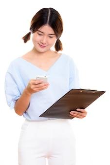 Młoda piękna kobieta azji przy użyciu telefonu komórkowego, trzymając schowek