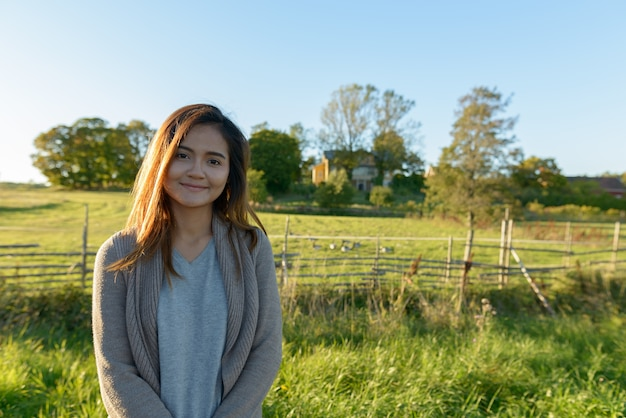 Młoda piękna kobieta azji stojącej w spokojnej trawiastej równinie z naturą