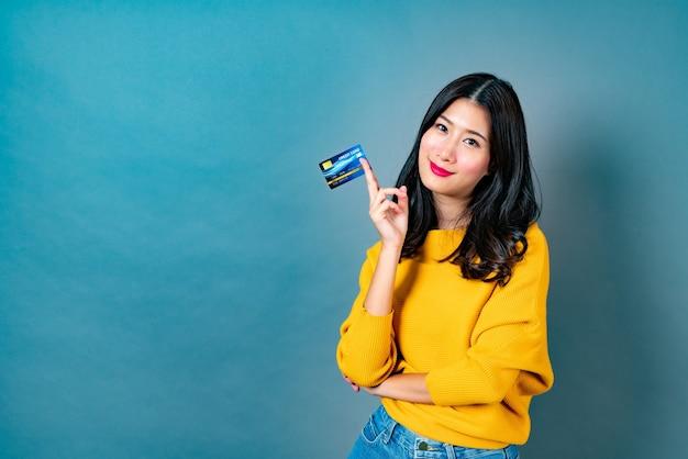 Młoda piękna kobieta azji uśmiecha się i przedstawia w ręku kartę kredytową, pokazując zaufanie i pewność przy dokonywaniu płatności na niebiesko