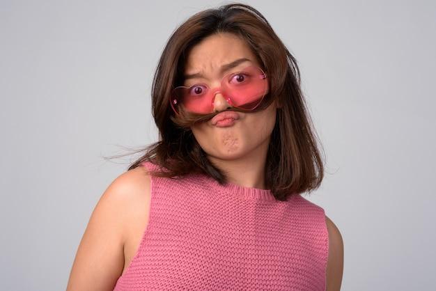 Młoda piękna kobieta azji w okularach w kształcie serca z włosami jak wąsy