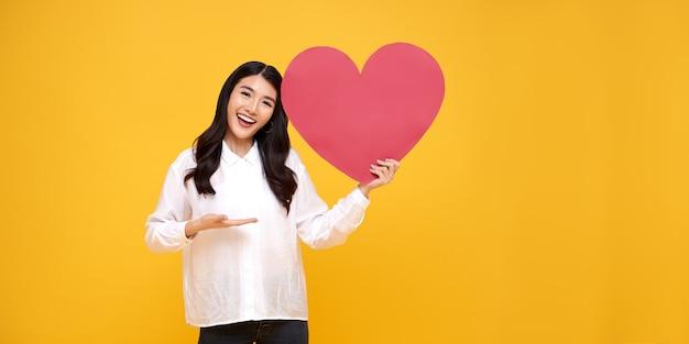 Młoda piękna kobieta azji wyświetlono czerwony znak serca na żółto. koncepcja miłości i szczęśliwych walentynek.