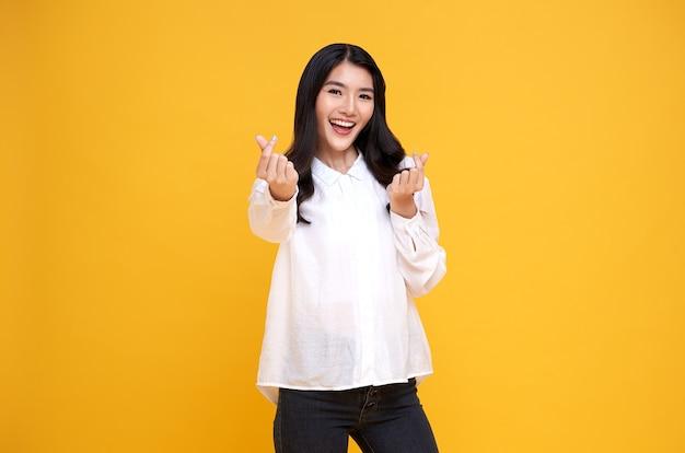 Młoda piękna kobieta azji wyświetlono mini serce znak na żółto. koncepcja miłości i szczęśliwych walentynek.
