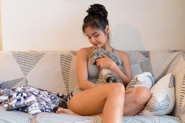 Młoda piękna kobieta azji z kotem siedzi na kanapie razem w domu