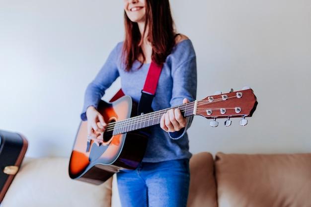 Młoda piękna kobieta bawić się gitary pozycję na kanapie.