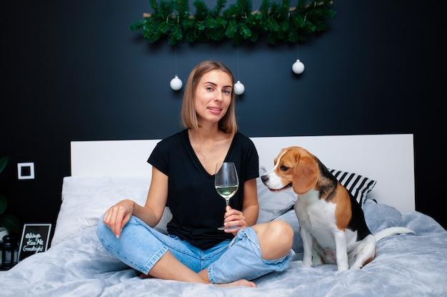 Młoda piękna kobieta bawić się z psim obsiadaniem na łóżku w stylowej sypialni. zwierzęta domowe w domu. pies beagle przyjaźń. komfortowa przytulność