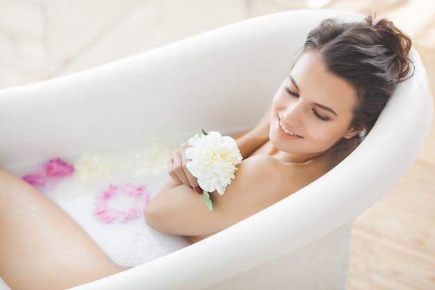 Młoda piękna kobieta bierze skąpanie z kwiatami i mlekiem