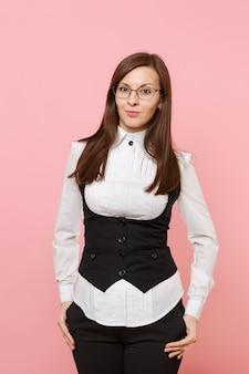 Młoda piękna kobieta biznesu w białej koszuli, garniturze i okularach, trzymając ręce w kieszeniach na białym tle na pastelowym różowym tle. szefowa. koncepcja bogactwa kariery osiągnięcia. skopiuj miejsce na reklamę.