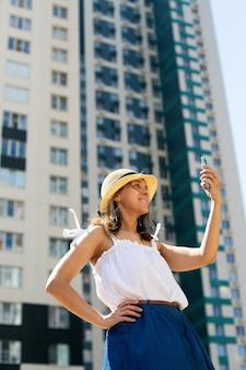 Młoda piękna kobieta blogger w letnie ubrania co selfie przed nowoczesnym budynkiem. format pionowy, nowoczesna kultura, słoneczny dzień, widok na miasto. kobieta ma na sobie kapelusz
