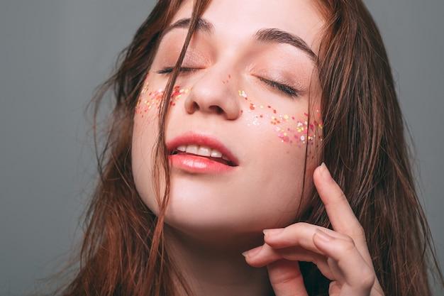 Młoda piękna kobieta. brokatowy trend w makijażu. błyszczy na policzkach. marzycielska ekspresja