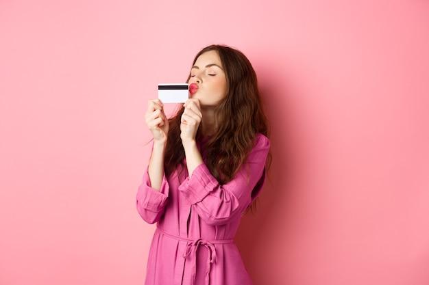 Młoda piękna kobieta całuje swoją kartę kredytową, idzie na zakupy, marnuje pieniądze w sklepach, stoi przed różową ścianą. skopiuj miejsce