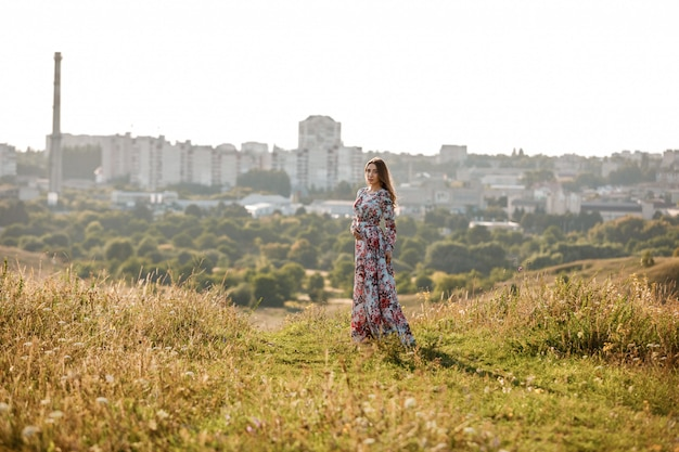 Młoda piękna kobieta chodzi w lata polu z trawą.