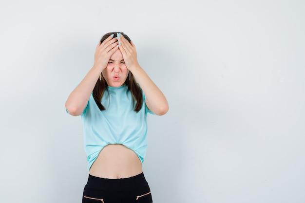 Młoda piękna kobieta cierpi na ból głowy w koszulce i wygląda na bolesną, widok z przodu.