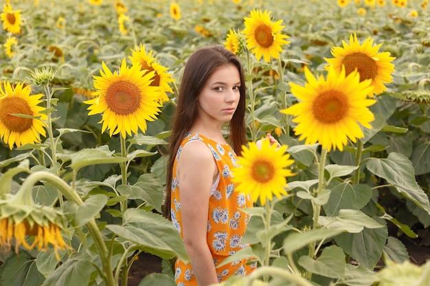 Młoda piękna kobieta ciesząca się latem, młodością i wolnością, trzymająca słoneczniki na tle błękitnego nieba. obraz stonowany.
