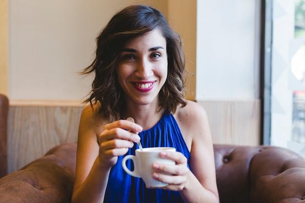 Młoda piękna kobieta cieszy się filiżankę kawy w kawiarni. poza tym laptop. niebieska sukienka na co dzień. współczesne życie w pomieszczeniu