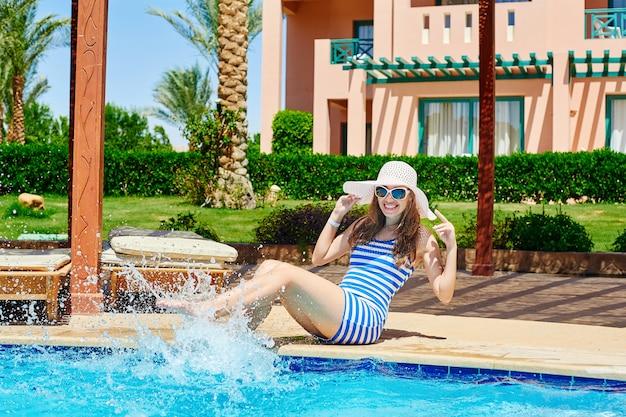 Młoda piękna kobieta cieszy się słońce i siedzi na krawędzi basenu