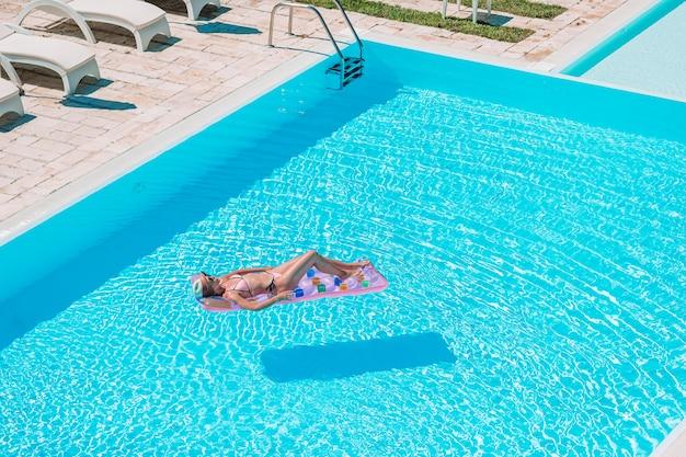 Młoda piękna kobieta cieszy się wakacje w luksusowym pływackim basenie