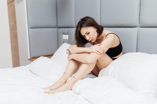 Młoda piękna kobieta czuje się gruba budząc się rano w swoim łóżku