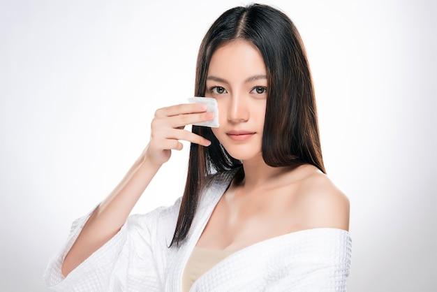 Młoda piękna kobieta czyści twarz bawełną