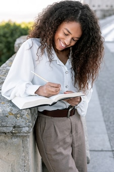 Młoda piękna kobieta czyta książkę outside