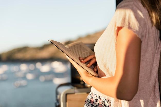Młoda piękna kobieta czytająca nad jeziorem