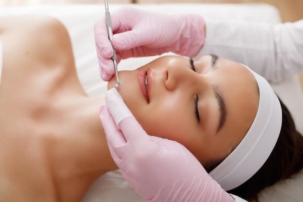 Młoda piękna kobieta dostaje zabieg oczyszczania twarzy w gabinecie kosmetycznym