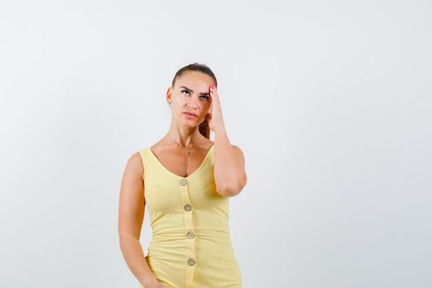 Młoda piękna kobieta dotyka twarzy palcami, patrząc w sukienkę i patrząc zamyślony. przedni widok.
