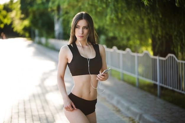 Młoda piękna kobieta działa w parku i słuchanie muzyki w słuchawkach