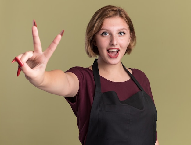 Młoda piękna kobieta fryzjer w fartuch patrząc z przodu pokazuje znak v uśmiechnięty stojący nad zieloną ścianą