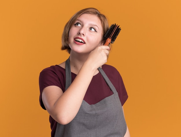 Młoda piękna kobieta fryzjer w fartuch trzymając szczotka do włosów czesanie włosów patrząc na bok uśmiechnięty stojący nad pomarańczową ścianą