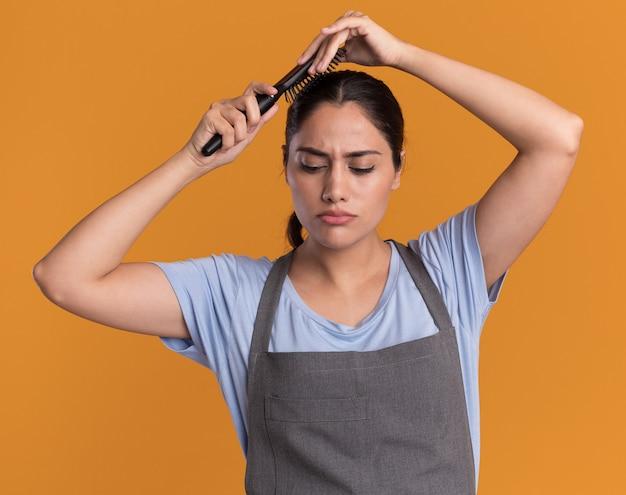 Młoda piękna kobieta fryzjer w fartuch, trzymając szczotka do włosów, czesząc jej włosy, stojąc na pomarańczowej ścianie
