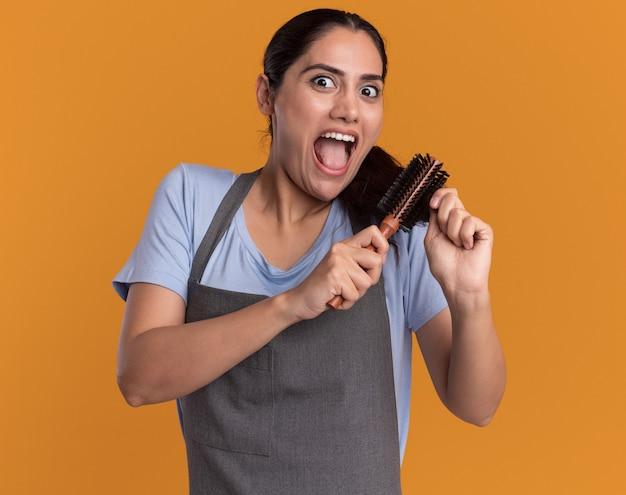 Młoda piękna kobieta fryzjer w fartuch, trzymając szczotkę do włosów, czesając włosy, szczęśliwa i podekscytowana, patrząc na przód stojący nad pomarańczową ścianą
