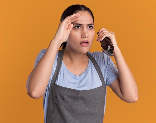 Młoda piękna kobieta fryzjer w fartuch trzymając trymer, patrząc uważnie na bok z ręką nad głową na pomarańczowej ścianie