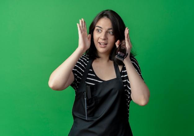 Młoda piękna kobieta fryzjerka w fartuch trzymając trymer patrząc na bok mylić stojąc na zielonej ścianie