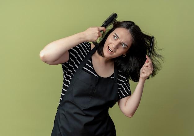 Młoda piękna kobieta fryzjerka w fartuch z grzebieniem szczotka tkwiącym we włosach na światło