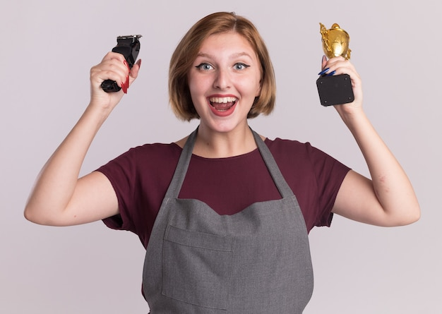 Młoda piękna kobieta fryzjerka w fartuchu trzyma trymer i złote trofeum patrząc z przodu szczęśliwa i podekscytowana stojąc nad białą ścianą