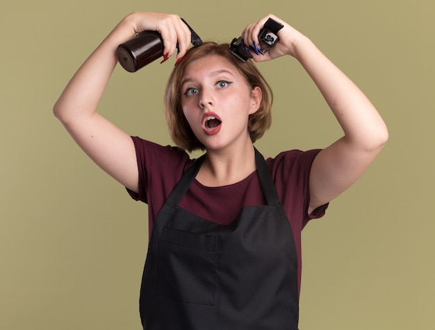 Młoda piękna kobieta fryzjerka w fartuchu trzymając butelkę z rozpylaczem i trymer próbuje obciąć włosy stojąc na zielonej ścianie